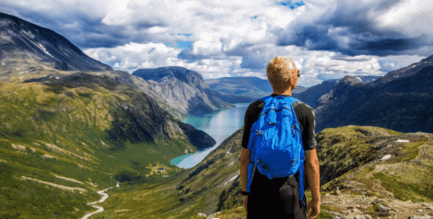 man with a backpack looking over mountain scenery