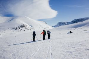 three people hiking in the snow