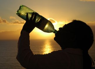 silhouette of a man drinking water from a bottle